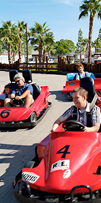 man and kids racing on go cart track