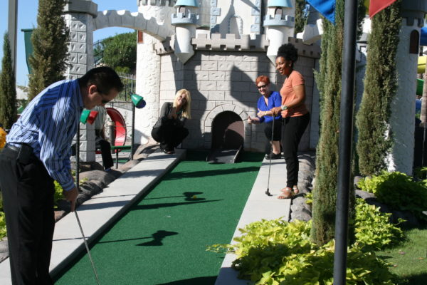 Group of adults playing mini golf at company party